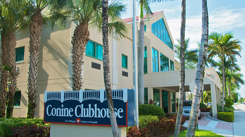 A modern light-colored building is shown with palm trees and a sign that reads Conine Clubhouse