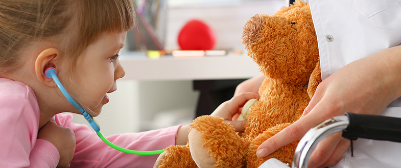 A young girl uses a stethoscope on a teddy bear