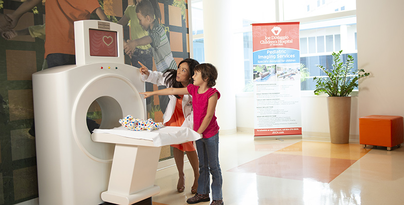 A child scans a teddy bear on a model CT scanner